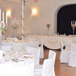 weiß gedeckte Tische, Stühle mit weißen Hussen überzogen, 5-armige Kerzenleuchter mit rosa Blumensträußen dekoriert