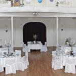 runde in weiß eingedeckte Tische, Stühle mit weißen Hussen