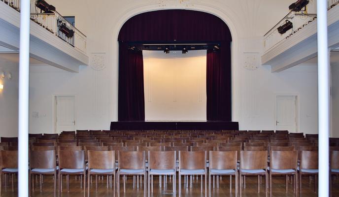 Jugenstilsaal mit Bestuhlung und Blick zur Bühne mit roten Samtvorhang