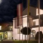 Nachtaufnahme des beleuchteten Hauses mit Fahnen im Vordergrund und Mond am Himmel