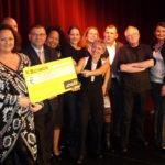 Künstlerinnen und Künstler stehen auf der Bühne und haben einen Scheck mit € 5.880,- in der Hand, glückliche Gesichter