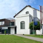 Jugendstilgebäude mit modernen Zubau, blauer Himmel mit wenigen Wolken