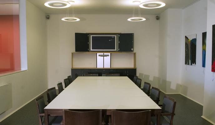 Raum mit großem Tisch, Stühlen und TV