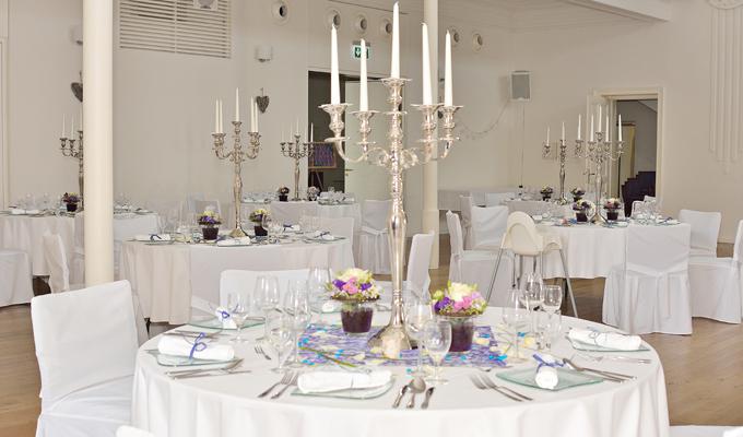 Blick auf viele runde Tische, weiß eingedeckt, Stühle mit weißen Hussen, Gläser und Teller am Tisch, 5-armige Kerzenleuchter