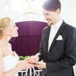 Braut im weißen Kleid und Bräutigam im scharzen Anzug halten einander an den Händen