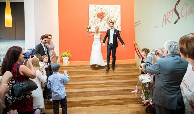 Brautpaar kommt die Stiegen von der Galerie herunter und wird von der Gästeschar fotografierend erwartet
