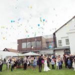 Hochzeitsgesellschaft lässt vor dem Konzerthaus Weinviertel bunte Luftballons steigen